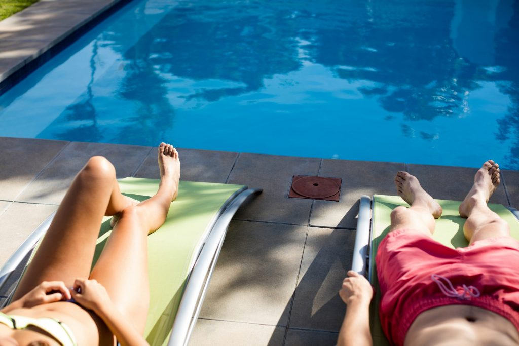 couple-relaxing-on-lounge-chair-at-poolside-8y546aj-scaled-1024x683
