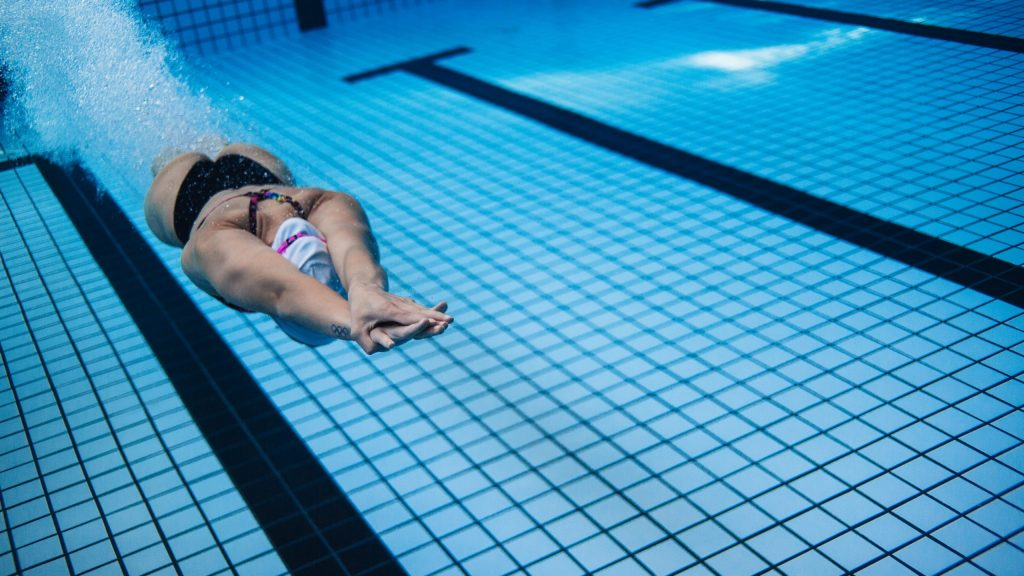 woman-training-in-swimming-pool-ptrgnzu-scaled-1024x576