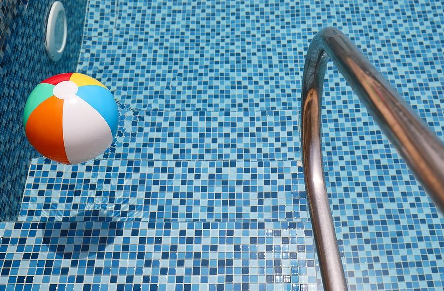 bigstock-beach-ball-in-pool-colorful-i-384363776